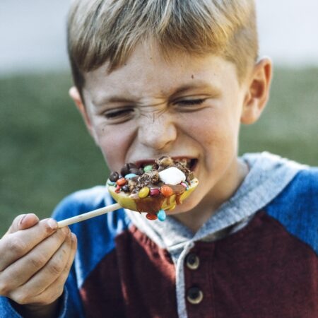 Kid eating apple with toppings