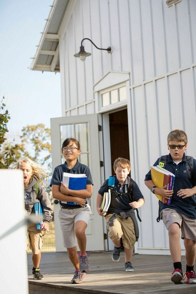 kids leaving schoolhouse with books